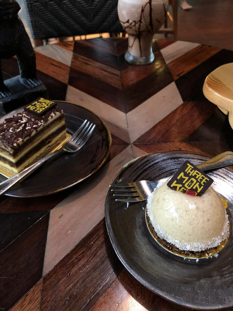 There are two black plates containing cake on a wooden table. One cake is a layered rectangle and one is a pale dome shaped cake.