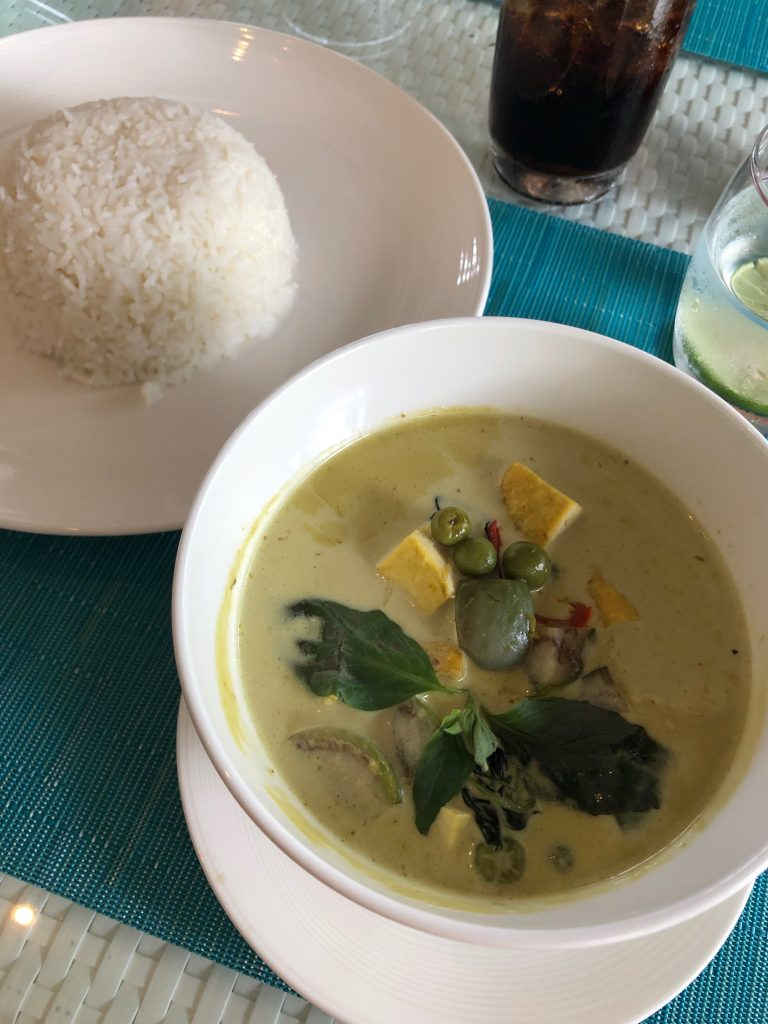 A white bowl containing Thai Green Curry and a plate with a dome of white rice