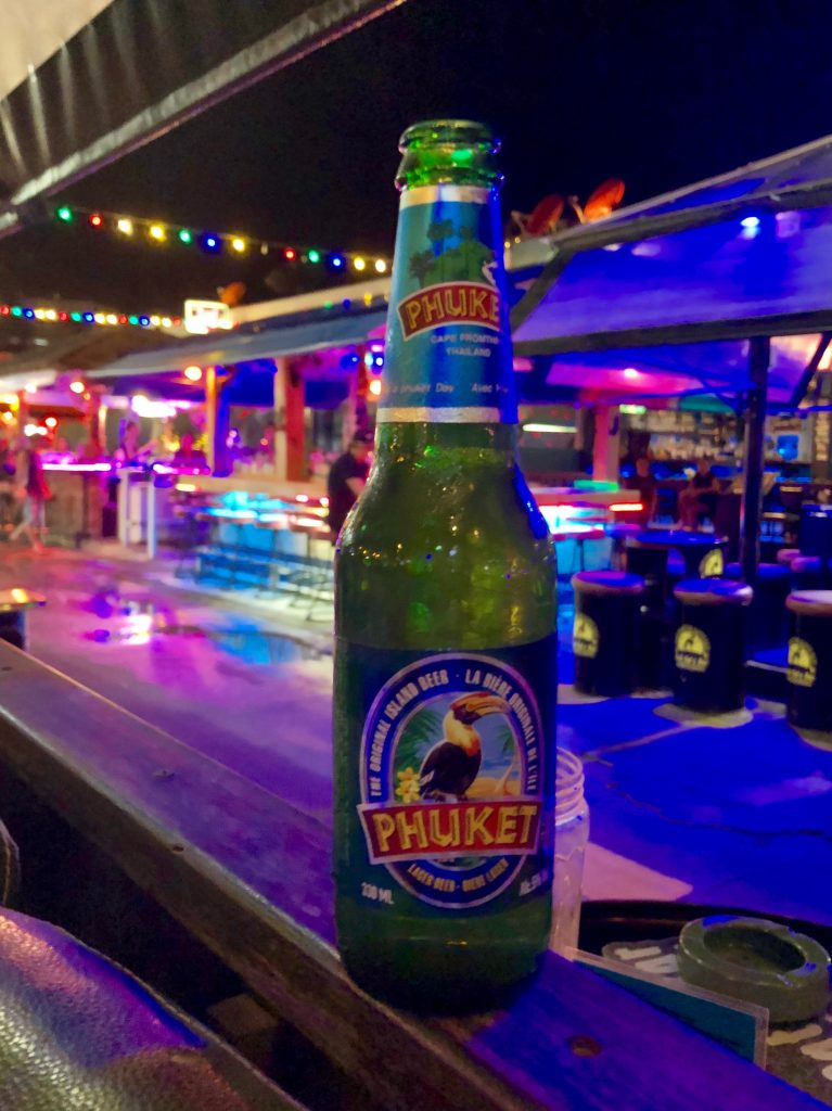 A green glass bottle labelled Phuket Beer stands on a wooden beam with the colourful lights of a strip of bars in the background