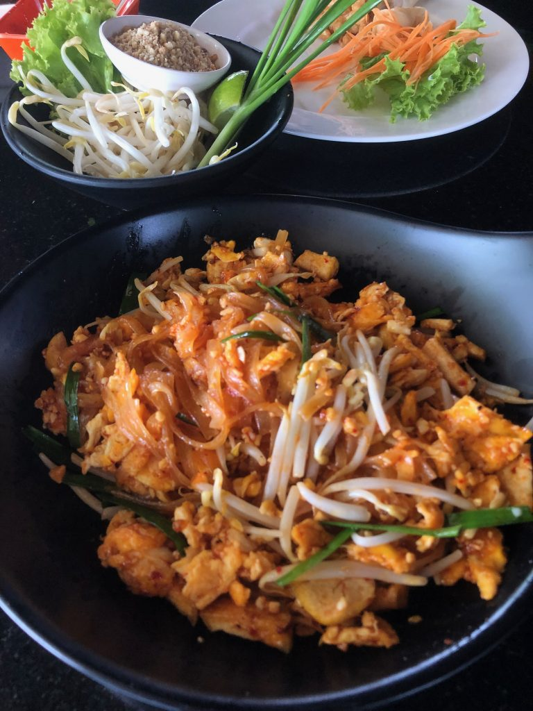 In the forefront of the photo is a black bowl contaning Pad Thai; a mix of noodles, vegetables, egg and beansprouts in an orange sauce. Behind