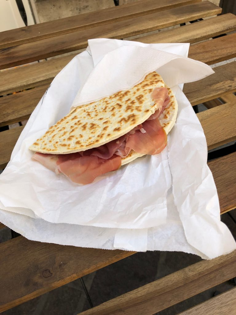 A folded piece of circular flat bread stuffed with parma ham laid onto a white paper bag on a dark brown wooden slotted table