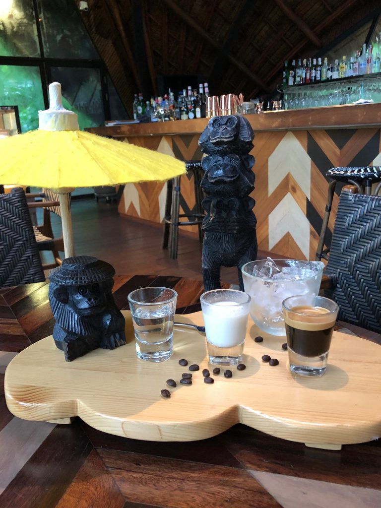 A wooden tray sits on a table holidng a glass tumbler filled with ice and a shot glass containing a clear liquid, a shot glass containing milk and a shot glass containing black coffee. The tray is decorated with scattered coffee beans and a wooden monkey statue