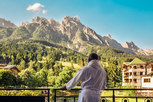 Man standing on terrace at Hotel Forsthofgut Leogang | Naturhotel | Austria