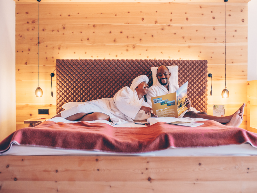 Couple in room reading magazine at Bio-Hotel Rupertus Leogang