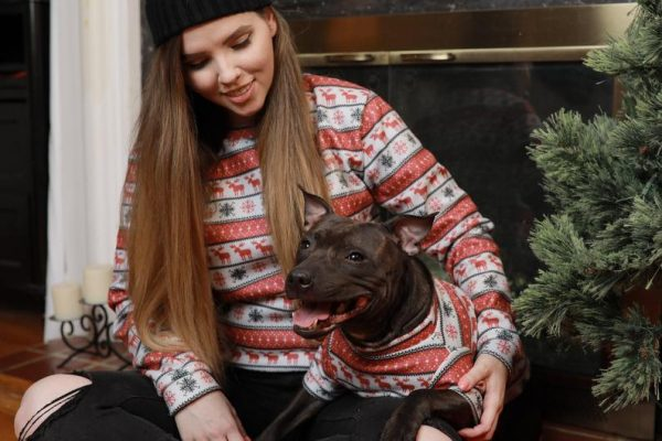 A woman and dog sit in front of a un-lit fire in matching Fair Isle festive tops