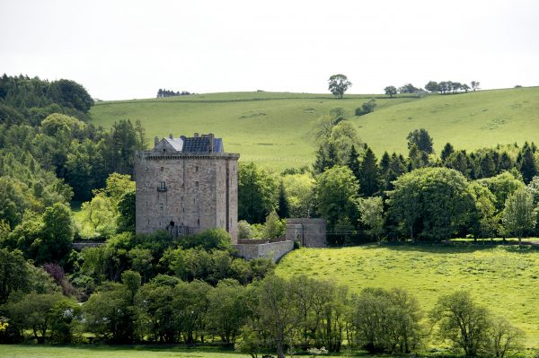 The tall stone square building of Borthwick Castle stands surroundec by green fields and trees